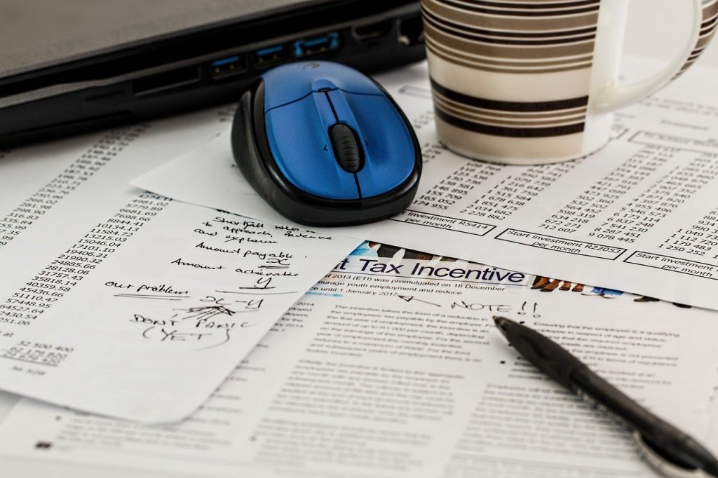 Computer mouse on desk covered with financial papers.