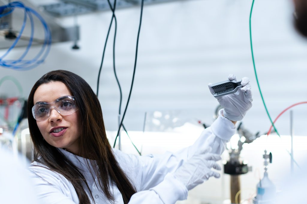 Woman in lab coat holds product prototype.