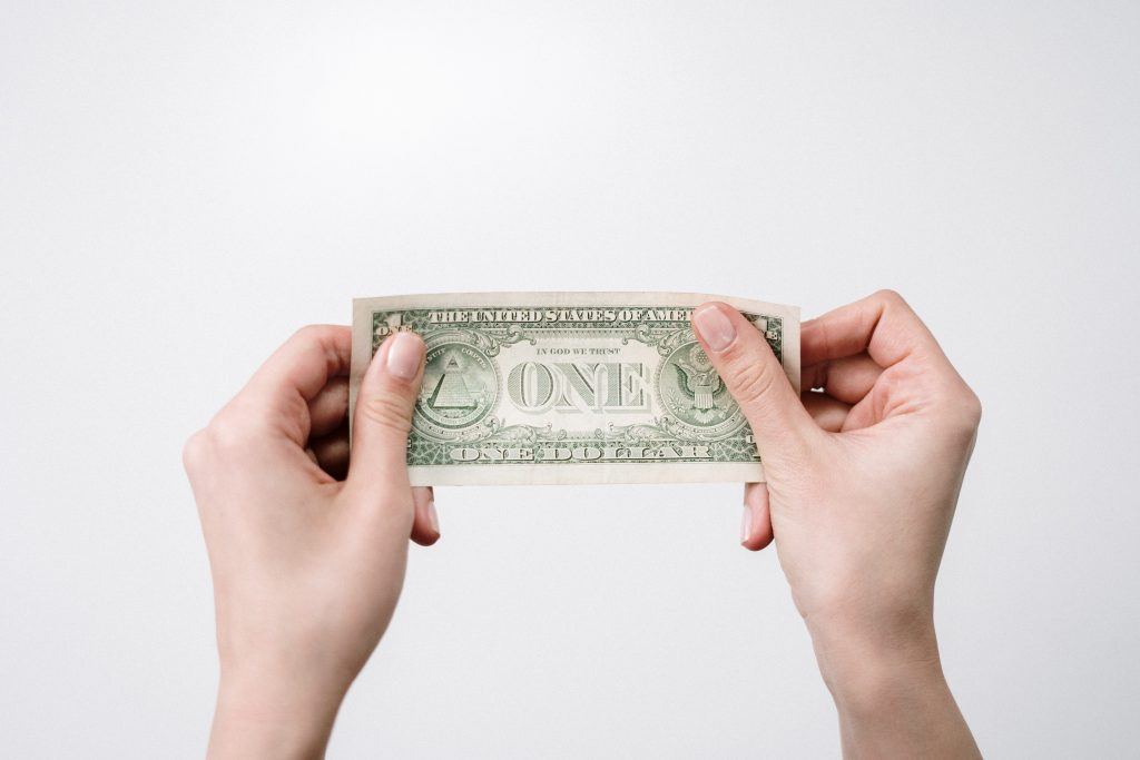 Woman's hands holding a dollar bill.