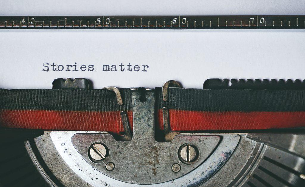 "Typewriter with paper reading ""Stories matter."""